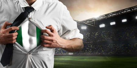 Nigeria soccer or football supporter showing flag under his business shirt on stadium.