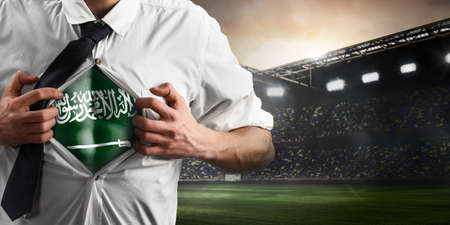 Saudi Arabia soccer or football supporter showing flag under his business shirt on stadium. Banque d'images