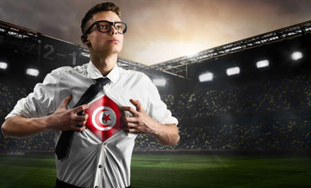 Tunisia soccer or football supporter showing flag under his business shirt on stadium. Stock fotó