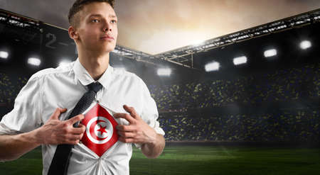 Tunisia soccer or football supporter showing flag under his business shirt on stadium. 版權商用圖片