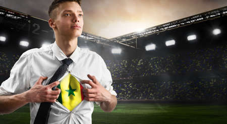 Senegal soccer or football supporter showing flag under his business shirt on stadium.