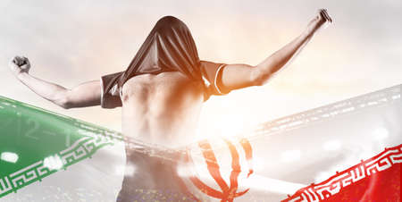 Iran national team. Double exposure photo of stadium and soccer or football player celebrating goal with his jersey on head