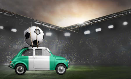 Nigeria flag on car delivering soccer or football ball at stadium Stock Photo