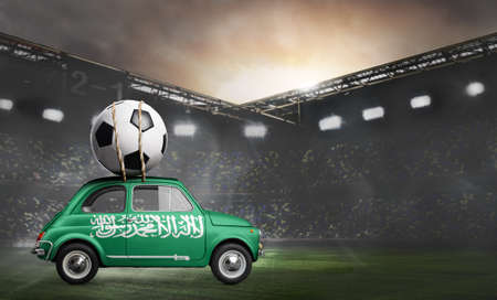Saudi Arabia flag on car delivering soccer or football ball at stadium Stock Photo