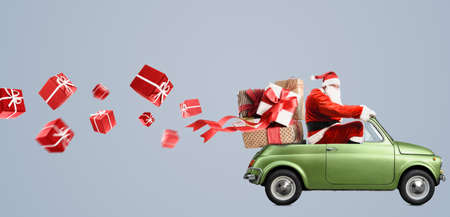 Babbo Natale in auto che consegna regali di Natale o Capodanno a sfondo grigio Archivio Fotografico