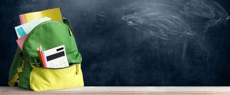 Retour à l'école sac à dos. Accessoires dans le sac d'étudiant contre tableau noir Banque d'images