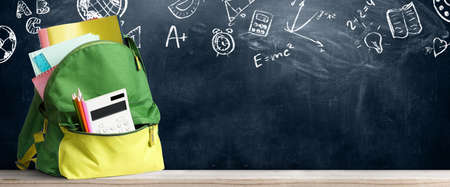 Back to school shopping baackpack. Accessories in student bag against chalkboard Stock Photo