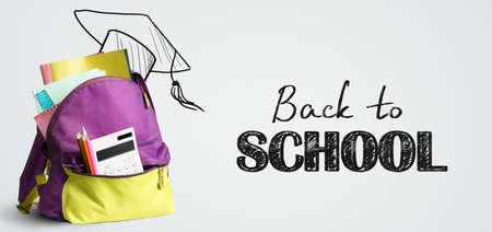 Mochila de compras de regreso a la escuela. Accesorios en bolsa de estudiante contra pizarra Foto de archivo