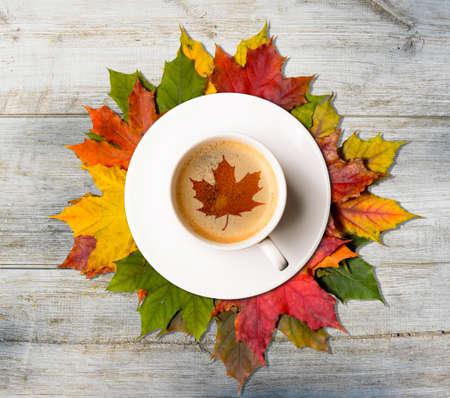 Tazza di caffè con il simbolo dell'acero su foglie colorate d'autunno sulla tavola di legno, vista dall'alto Archivio Fotografico