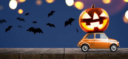 Halloween car delivering pumpkin against night scary autumn forest background Stockfoto