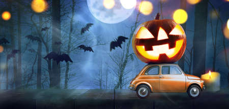 Halloween car delivering pumpkin against night scary autumn forest background Banque d'images