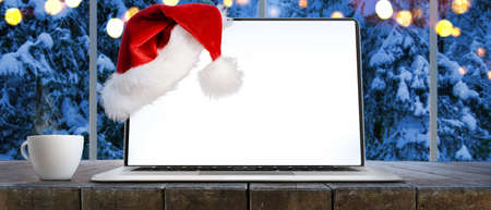 Laptop on table with Santa Claus hat at home with panoramic view through window of snowy trees in winter forest, screen is cut with provided clipping path Imagens