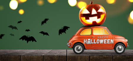 Halloween car delivering pumpkin against green background Stock Photo
