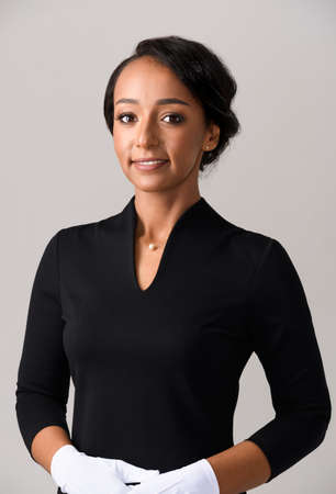 Flight attendant in black dress and white gloves. Smiling African woman stewardess on gray background.