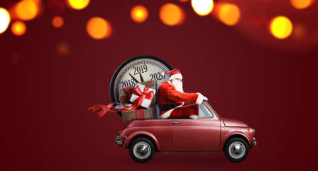Christmas countdown arriving. Santa Claus on car delivering New Year gifts and clock at red background Stock Photo