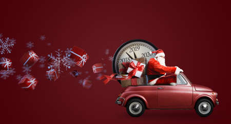 Christmas countdown arriving. Santa Claus on car delivering New Year gifts and clock at red background 免版税图像