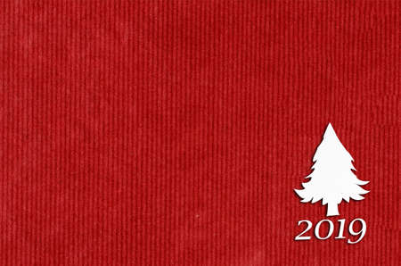 Cut paper in fir-tree shape for christmas card or new year background on red table Archivio Fotografico