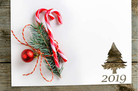 Cut paper in fir-tree shape for 2019 christmas card or new year background on wooden table Archivio Fotografico - 113928316