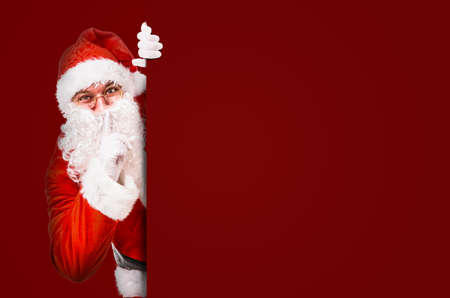Santa Claus with finger on lips asking for silence with colorful advertisement board and copy space