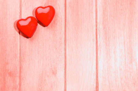 Couple of glossy red hearts for Valentines day on living coral colored wooden table Stok Fotoğraf