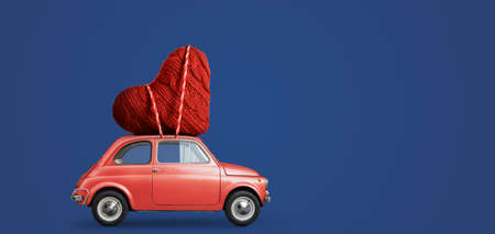 Living coral retro toy car delivering craft heart for Valentines day on blue background Standard-Bild