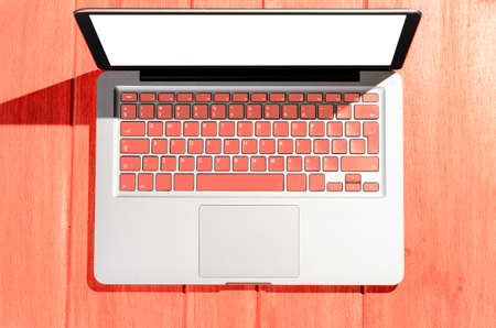 Laptop with living coral colored keyboard on wooden table on a sunny day, view from above