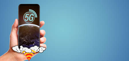 male hand hold launching 5G smartphone with planet Earth on screen, isolated on blue background. Stock Photo