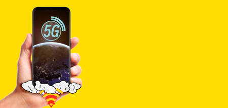 male hand hold launching 5G smartphone with planet Earth on screen, isolated on yellow background. Stock Photo