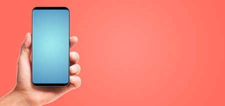 male hand holding bezel-less smartphone with blank screen, on living coral background