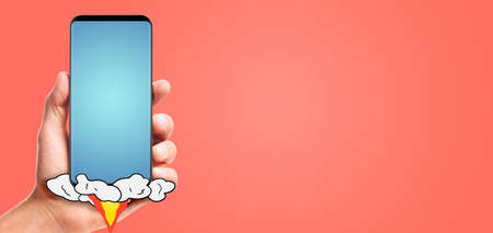 male hand hold launching smartphone with blank blue screen, on living coral background.
