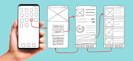 UI development. Male hand holding smartphone with wireframed user interface screen prototypes of a mobile application on blue background.