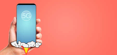 male hand hold launching 5G smartphone, on living coral background. Stockfoto