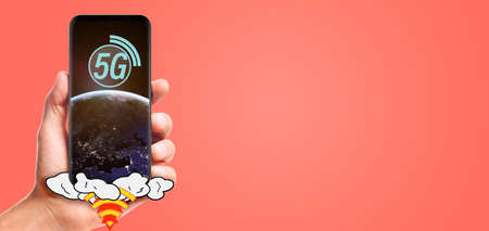 male hand hold launching 5G smartphone with planet Earth on screen, isolated on living coral background.