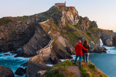 Couple against San Juan de Gaztelugatxe, its medieval stairs and bridge at sunrise, Basque Country, Spain 免版税图像