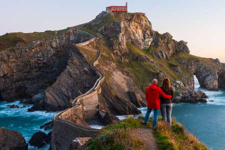 Couple contre San Juan de Gaztelugatxe, son escalier médiéval et son pont au lever du soleil, Pays Basque, Espagne Banque d'images