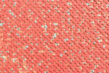 Sequin fabric background. Close-up shot of glittery living coral sequins texture