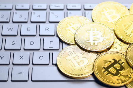 Bitcoin cryptocurrency. Golden coins on laptop keyboard, macro shot