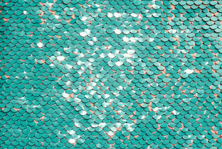 Sequin fabric background. Close-up shot of glittery blue or aquamarine colored sequins texture with coral dots Banque d'images