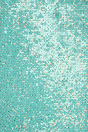 Sfondo di tessuto di paillettes. Primo piano di una trama di paillettes luccicanti blu o acquamarina con punti di corallo