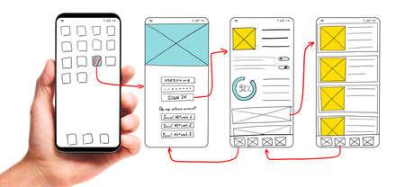 Desarrollo de UI. Mano masculina que sostiene el teléfono inteligente con prototipos de pantalla de interfaz de usuario con estructura de alambre de una aplicación móvil sobre fondo blanco. Foto de archivo