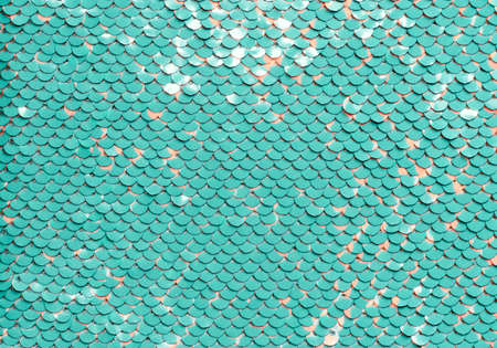 Sequin fabric background. Close-up shot of glittery blue or aquamarine colored sequins texture with coral dots Standard-Bild