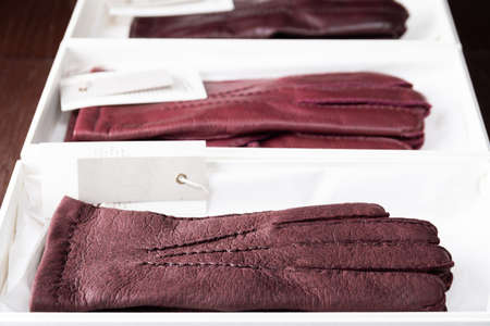 Burgundy leather gloves in boxes at luxury clothing boutique store.