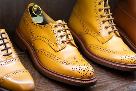 Tan full grain leather brogues shoes set on wooden display in in men shoes boutique store. Stok Fotoğraf