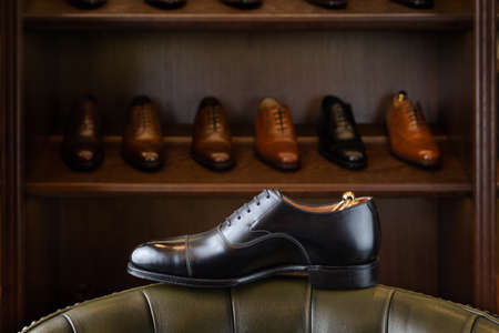 Black full grain leather shoe in front of wooden display in men shoes boutique store. Stok Fotoğraf