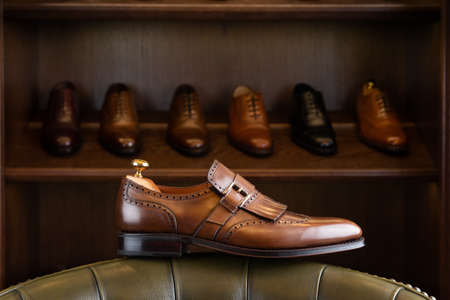 Brown full grain leather shoe in front of wooden display in men shoes boutique store. Stok Fotoğraf