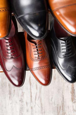 Zapatos de cuero de plena flor negros y marrones en exhibición de madera en tienda boutique de zapatos para hombres.