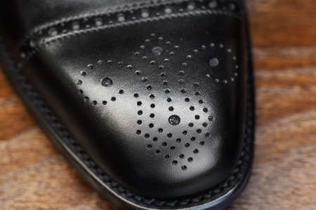 Black brogue toe of men full grain leather shoe, close up