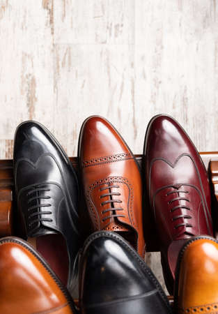 Black and brown full grain leather shoes on wooden display in in men shoes boutique store.