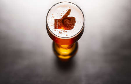 Best beer concept. Thumbs up symbol on beer glass foam on black table, view from above