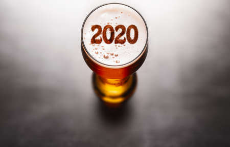 New Year beer. 2020 symbol on beer glass foam on black table, view from above